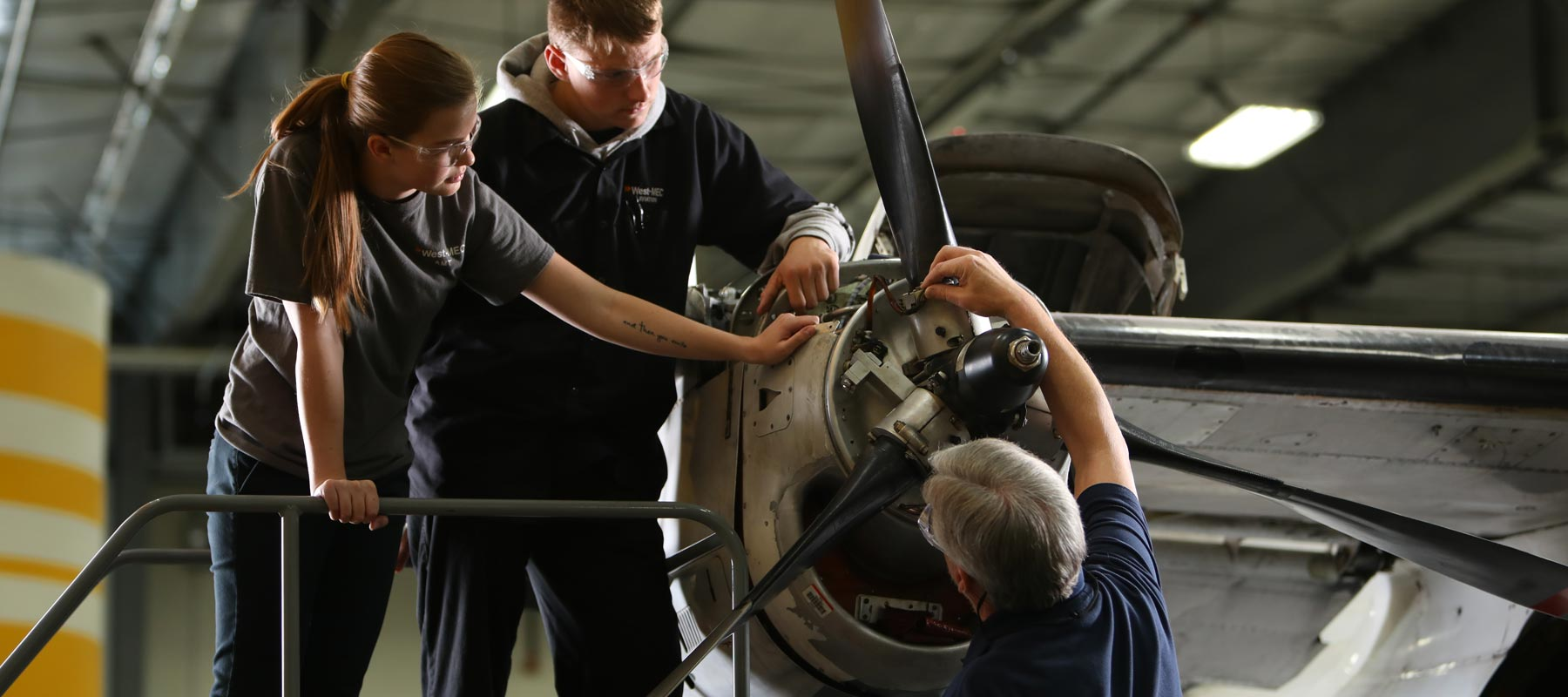 photo of students & instructor working on an airplane