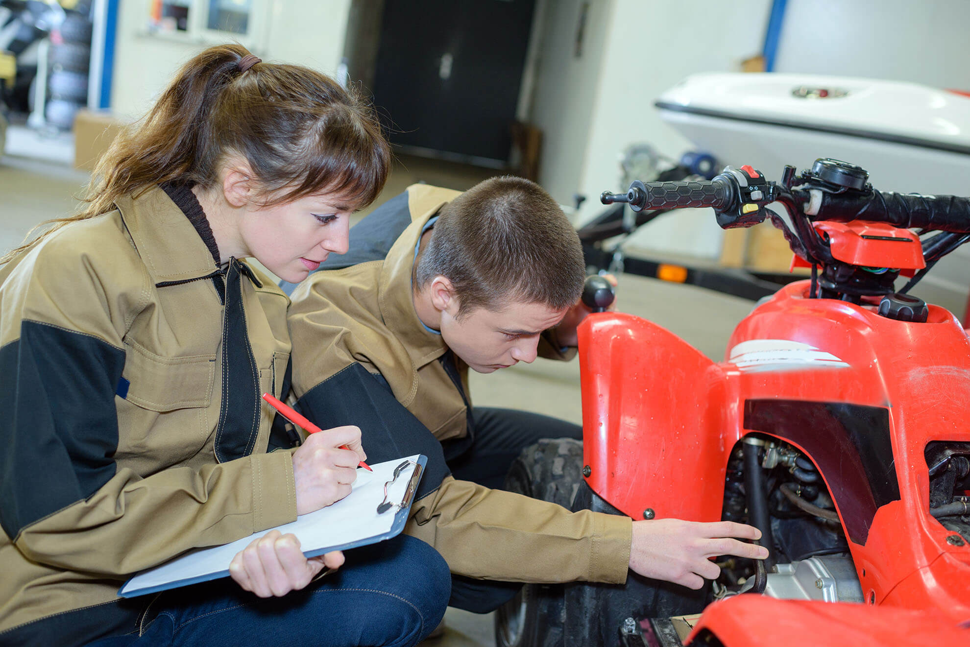 young mechanics examining quad bike
