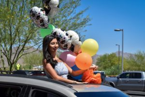 Photo: graduate holding balloons