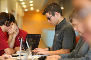 Photo of a coding student on his laptop, surrounded by other students.